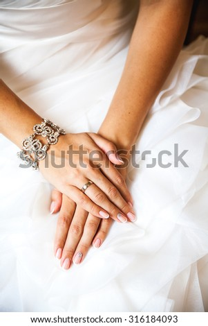 Hands of the bride on a wedding dress. French manicure. Wedding Fashion - stock photo