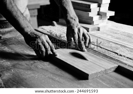 hands of the craftsman cut a piece of wood - stock photo