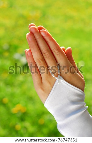 hands of the girl going to the First Holy Communion set in amen  against green grass background - stock photo