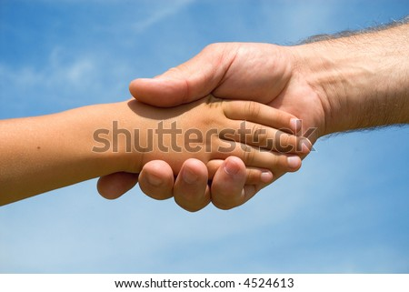 Hands of the grandfather and grandson on a background of blue sky - stock photo