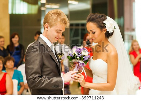 Hands of the groom and bride is wearing a ring on  finger. Wedding ceremony. Gold, symbol, religion, love. - stock photo