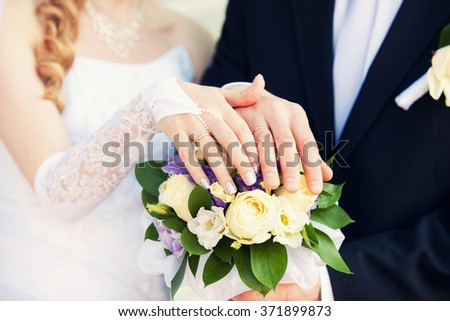 hands of the groom and the bride on a wedding bouquet from roses - stock photo
