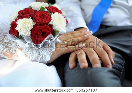 Hands of the groom and the bride with wedding rings and a wedding bouquet from roses  and chrysanthemums - stock photo