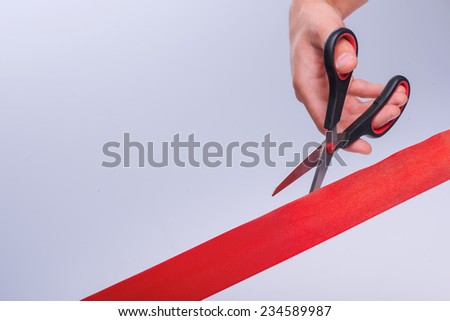 Hands of the man cut the red band. Concept of the new life - stock photo
