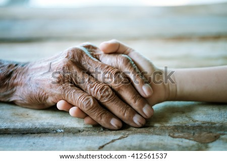 Hands of the old man and a child's hand on the wood table - stock photo