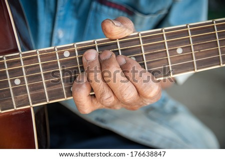 hands of the old man hold guitar - stock photo