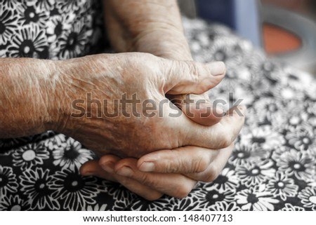 Hands of the old woman. Senior's hands. Hands of an 82-year-old woman resting on lap - stock photo