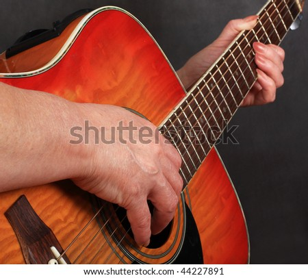 Hands of the woman playing a guitar - stock photo