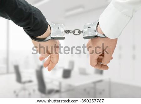 Hands of two men fixed in handcuffs. Close up. Blurred office background. Concept of accessory of crime. - stock photo