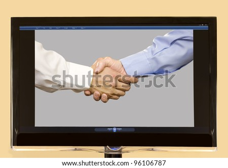 Hands of two White males shaking hands shown on LCD screen. - stock photo
