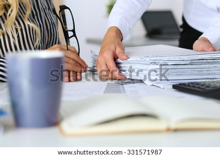 Hands of two women in office. Employee showing pack of documents to manager or boss giving extra work to executor. Overwork, overtime, deadline, paperwork, project approval, teamwork concept - stock photo