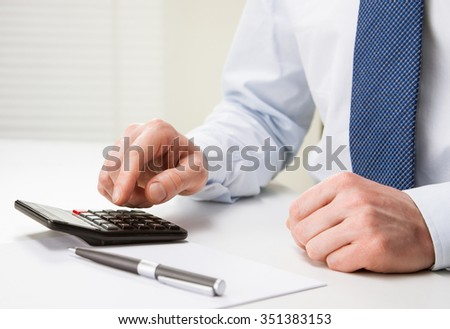 Hands of unrecognizable businessman using calculator - closeup shot - stock photo