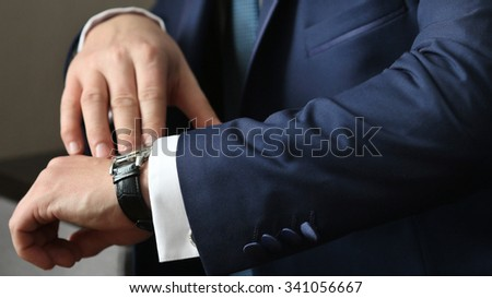 Hands of wedding groom getting ready in suit, selective focus - stock photo
