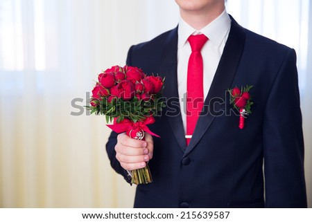 Hands of wedding groom getting ready in suit. The groom holds wedding bouquet. - stock photo