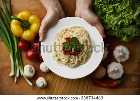 Hands of woman chef serving plate with spaghetti and tomato sauce decorated with green basil. Top view of wooden table with mediterranean meal, vegetables and salad.   - stock photo