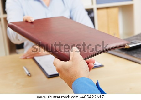 Hands of woman giving application portfolio to HR man in office - stock photo