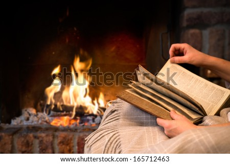 hands of woman reading book by fireplace - stock photo