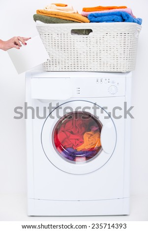 Hands of woman with detergent. Washing machine and clothes on the white background. - stock photo