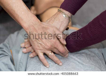 Hands of women are seen on a mannequin during an exercise of resuscitation - stock photo