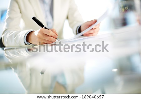 Hands of young businesswoman signing paper - stock photo