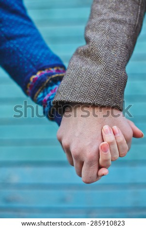 Hands of young couple over blue background - stock photo