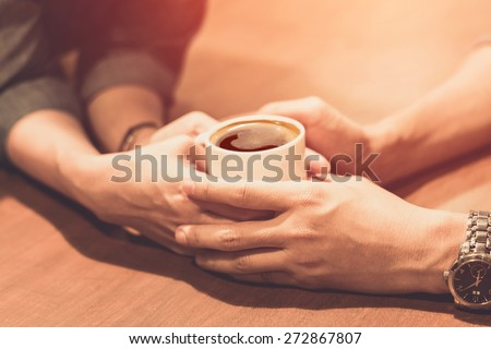 hands of young lovers holding a hot cup of coffee - stock photo