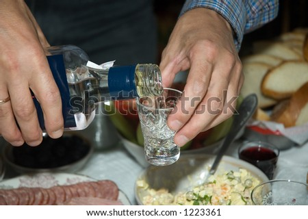 hands of young man filling up glass with vodka - stock photo