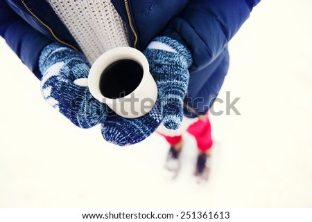 Hands of young woman holding a cup of coffee outside in snow - stock photo