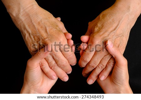 Hands of young woman holding hands of an elderly woman on black, top view - stock photo