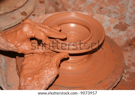 hands on a pot wheel - stock photo