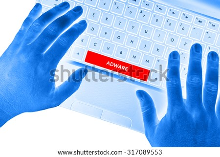 """Hands on laptop with """"ADWARE"""" word on spacebar button on white background. - stock photo"""