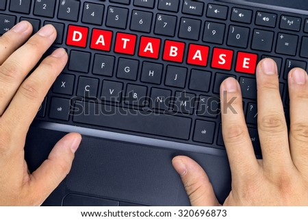 "Hands on laptop with ""DATABASE"" word on keyboard buttons. - stock photo"