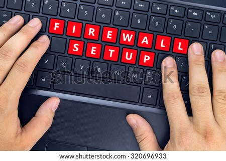 """Hands on laptop with """"FIREWALL SETUP"""" words on keyboard buttons. - stock photo"""