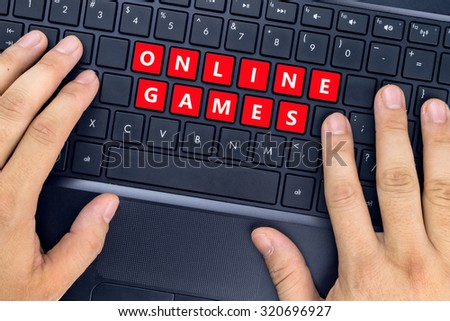 "Hands on laptop with ""ONLINE GAMES"" words on keyboard buttons. - stock photo"