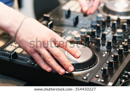 hands on the DJ decks. Man makes music for dancing in the club. Mixer with vinyl record at party - stock photo
