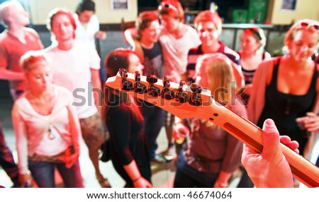 Hands on the fretboard of an electric guitar in a nightclub with people dancing in the background - stock photo