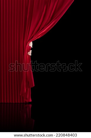 Hands opening a realistic stage curtains on a black background. Ideal composition to place text on the black background. - stock photo