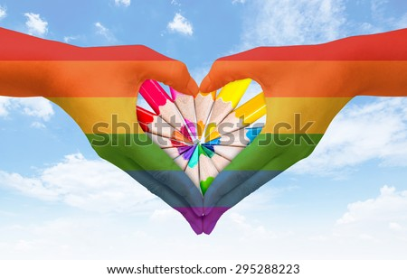Hands painted as the rainbow flag forming a heart, symbolizing gay love on blue sky. Freedom concept. - stock photo