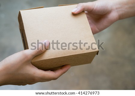 hands passing and receiving small brown box - stock photo