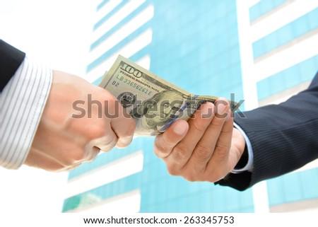 Hands passing money, US dollar (USD) bills - soft focus - stock photo