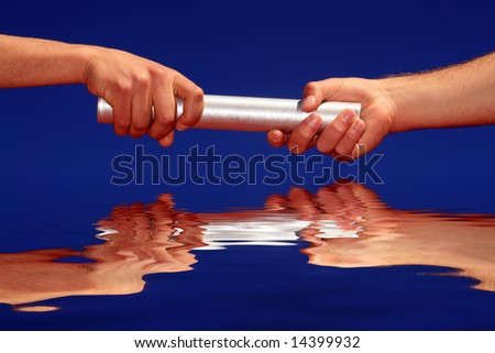 hands passing the batton against blue sky - stock photo