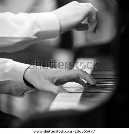 Hands pianist playing on a grand piano in black and white - stock photo