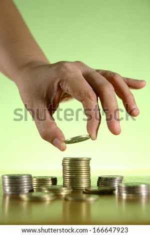 Hands Piling Coins Photo of a hand piling or stacking coins - stock photo