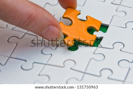 Hands placing last piece of a Puzzle - stock photo