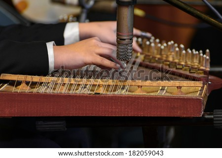 Hands Playing Arabian Qanon Musical Instrument During a Symphony - stock photo