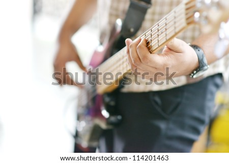 Hands playing electric guitar, focus on finger - stock photo