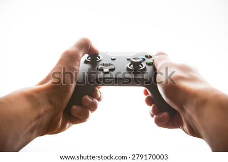 hands playing joystick, white light background - stock photo