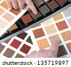 Hands pointing to sample color chart - stock photo