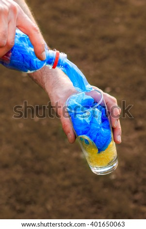 Hands pouring from plastic water bottle full of plastic shopping bags in glass. Concept image for polluting water and oceans with plastic waste. Copy space - stock photo
