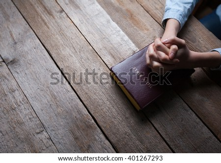hands praying with a bible in a dark over wooden table - stock photo